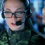 Military control room console operator talking into microphone
