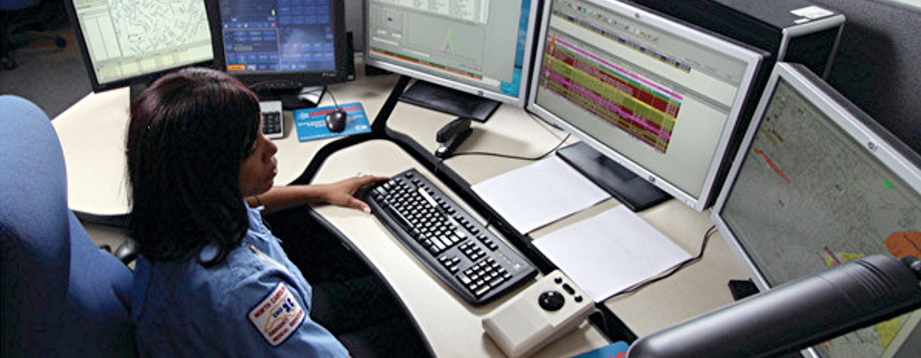 emergency operator sitting at console desk looking at monitors